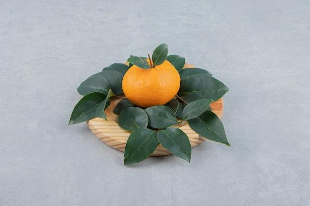 Pojedyncza świeża mandarynka z liśćmi na drewnianym talerzu