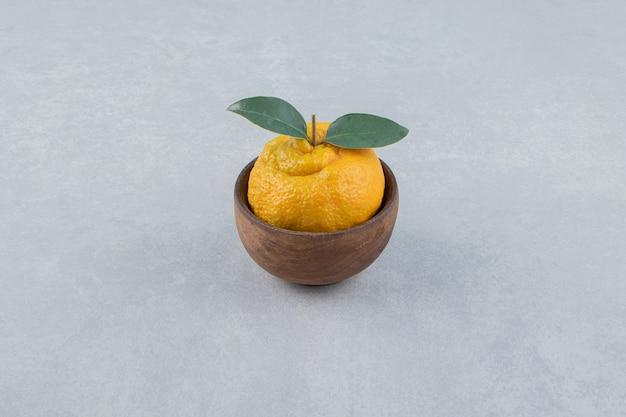 Pojedyncza świeża mandarynka z liśćmi w drewnianej misce.