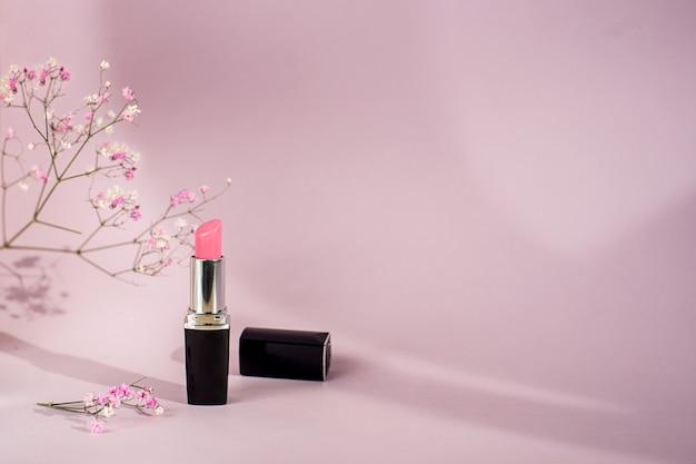 Pojedyncza tubka różowej szminki na różowym tle z kwiatami