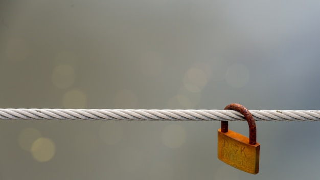 Pojedyncza zardzewiała kłódka wisi na drucie.