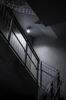 Pojedyncza żarówka oświetlająca wewnętrzne ciemne schody