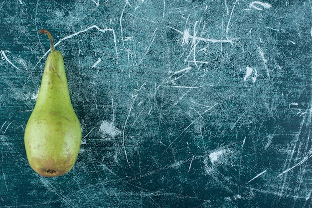 Pojedyncza zielona gruszka na marmurowym stole.