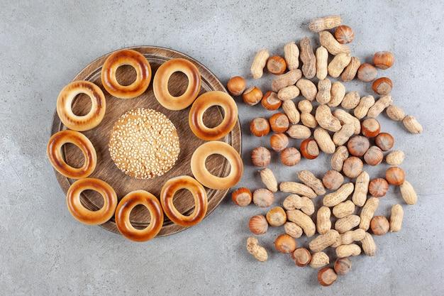Pojedyncze ciastko otoczone sushki na drewnianej desce obok rozrzuconego asortymentu orzechów na marmurowej powierzchni.