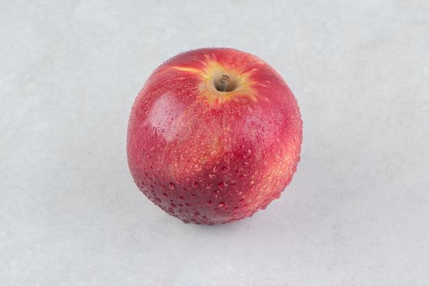 Pojedyncze czerwone jabłko na kamiennym stole.