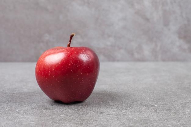 Pojedyncze czerwone jabłko na marmurowej powierzchni