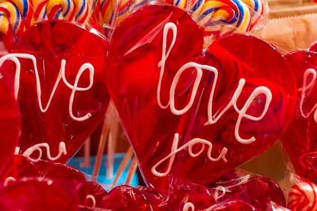 Pojedyncze czerwone lollypop cukierek z białym tekstem. kocham cię lolly ze ścieżką przycinającą