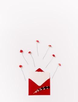 Pojedyncze czerwone róże papieru i koperty z wtapianiem na białym tle z miejsca kopiowania