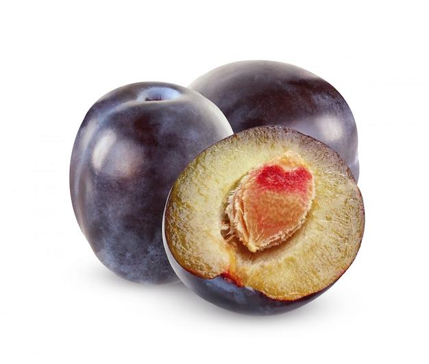 Pojedyncze fioletowe śliwki. dwie całe owoce i pół na białym