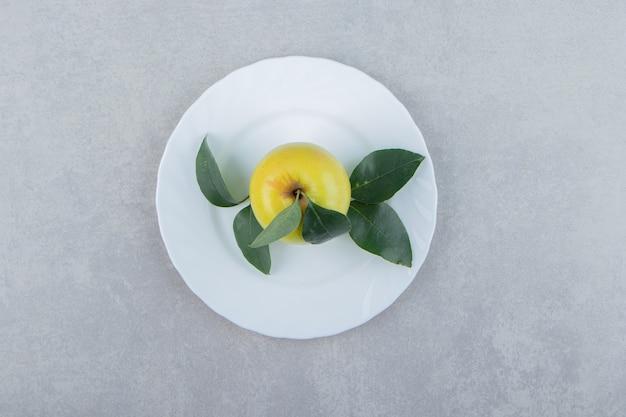 Pojedyncze jabłko z liśćmi na białym talerzu.