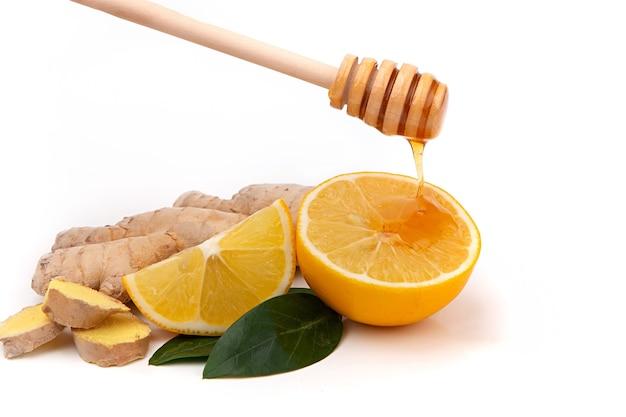Pojedyncze kawałki imbiru i cytryny z miodem. medycyna naturalna, składniki przeciwgrypowe i przeciwwirusowe na białym tle.