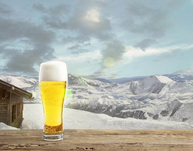 Pojedyncze piwo jasne w szkle i krajobraz gór na tle. napój alkoholowy i słońce, a przed nim czyste niebo. ciepło w wiosenny dzień, wakacje, podróże, czas przygody.