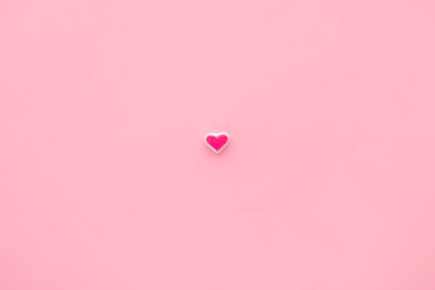 Pojedyncze serce kandyzowanego na tle różowy