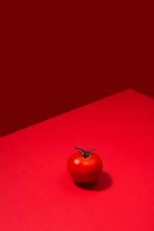 Pojedyncze świeże pomidory przedstawione na czerwonym stole