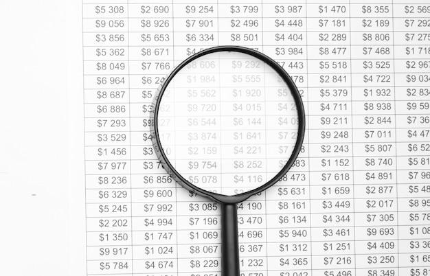 Pojedyncze szkło powiększające z czarnym uchwytem, oparte na danych finansowych. koncepcja badań biznesowych i finansowych.