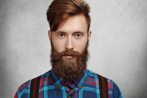 Pojedyncze ujęcie atrakcyjnego modnego mężczyzny rasy kaukaskiej z rozmytą brodą i wąsami hipster w koszuli w kratkę, patrząc z poważnym i zamyślonym wyrazem twarzy, myśląc o czymś