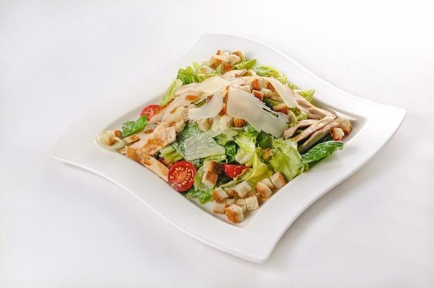 Pojedyncze ujęcie białego talerza z sałatką cezar - idealne do wykorzystania na blogu kulinarnym lub w menu