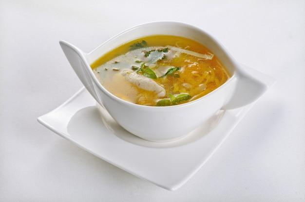Pojedyncze ujęcie białej miski z gorącą i kwaśną zupą - idealne na blog kulinarny lub do menu