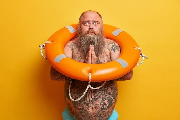 Pojedyncze ujęcie błagającego mężczyzny ściska dłonie, prosi o pozwolenie, ma wytatuowane ciało, duży brzuch, pozuje z nadmuchanym kołem ratunkowym, odizolowane na żółtej ścianie. facet z nadwagą idzie pływać