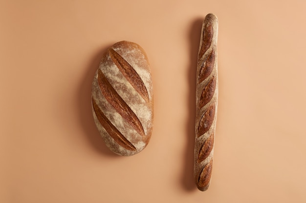 Pojedyncze ujęcie bochenka chleba i bagietki z organicznej mąki, na bazie zakwasu. tradycyjna piekarnia francuska. widok z góry. bezglutenowe świeże pieczywo domowej roboty. różne rodzaje, różnorodność potraw