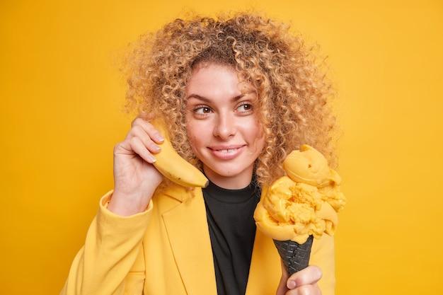 Pojedyncze ujęcie całkiem zadowolonej kobiety z kręconymi włosami ma przemyślany zadowolony wyraz zjada pyszne lody stożkowe trzyma banana w pobliżu ucha stawia przed żółtą ścianą. koncepcja czasu letniego
