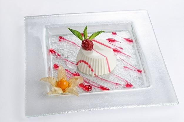 Pojedyncze ujęcie deseru panna cota z malinami - idealne do wykorzystania na blogu kulinarnym lub w menu