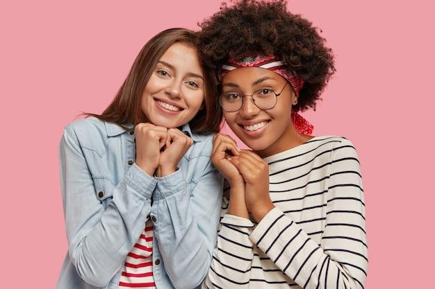 Pojedyncze ujęcie dwóch zadowolonych, wieloetnicznych młodych kobiet stoi blisko siebie, ma uśmiechy