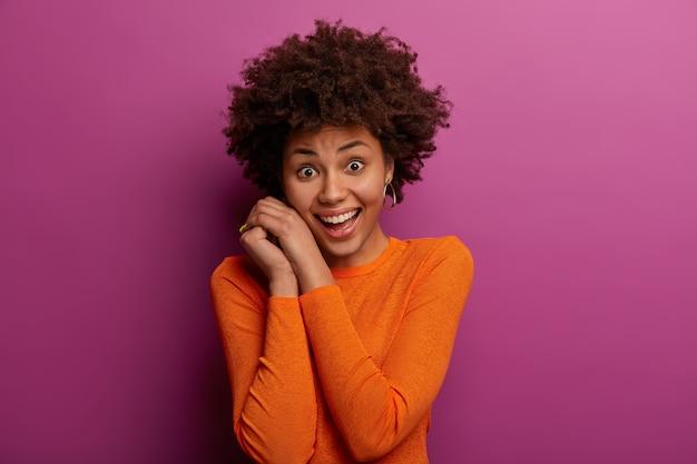 Pojedyncze ujęcie ładnej etnicznej młodej kobiety trzyma ręce blisko twarzy, uśmiecha się przyjemnie, jest w dobrym nastroju, ubrana w swobodny pomarańczowy sweter, ma naturalne kręcone włosy, pozuje na fioletowej ścianie