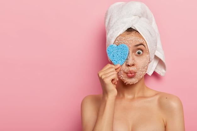 Pojedyncze ujęcie ładnie wyglądającej kobiety zakrywa oczy gąbką, utrzymuje zaokrąglone usta, ma nagie, zadbane ciało, ma zabrudzone oczy, nosi biały ręcznik, odizolowane na różowym tle, puste miejsce na bok