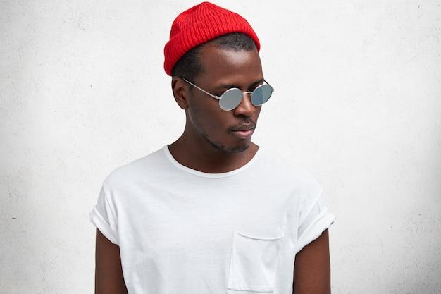 Pojedyncze ujęcie modnego poważnego młodego mężczyzny afroamerykanów w okularach przeciwsłonecznych, czerwonym modnym kapeluszu i dorywczo t shirt, wygląda na bok, na białym tle nad białym studio