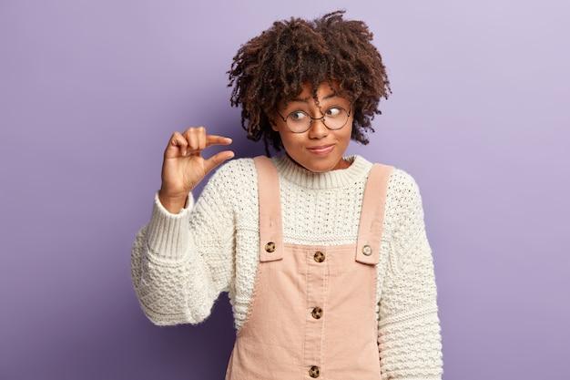 Pojedyncze ujęcie niezadowolonej, ciemnoskóra młoda kobieta robi mały gest ręką, mierzy mały przedmiot, ma zdezorientowany wyraz twarzy, nosi biały sweter, różowy kombinezon, demonstruje drobiazg