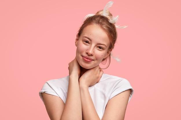 Pojedyncze ujęcie pięknej kobiety o zdrowej skórze, trzymającej dłonie na szyi, pozytywnie uśmiechającej się, ładnie wyglądającej, z piórami we włosach, ubrana na co dzień w białą koszulkę, słyszy coś dobrego. koncepcja spania
