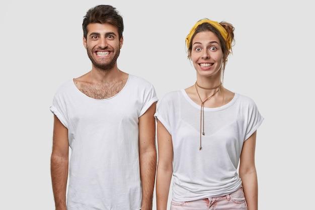 Pojedyncze ujęcie pozytywnych współpracowników z zabawnymi, szczęśliwymi minami, pokazujące białe zęby, szeroko uśmiechnięte, ubrane w zwykłe ubrania, pozujące na ścianie, wyrażające szczęście