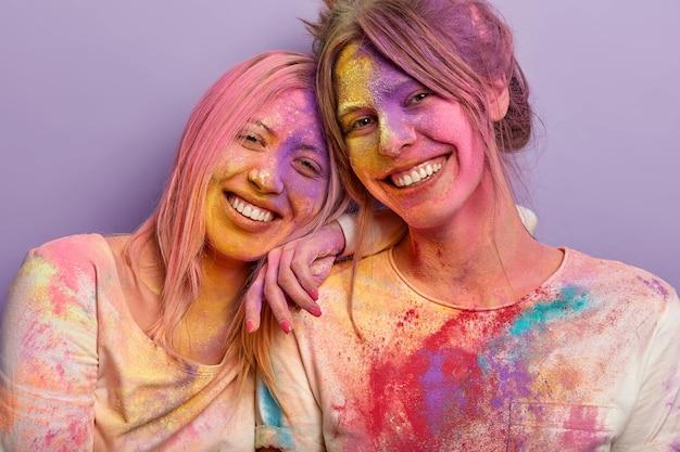 Pojedyncze ujęcie przyjaznych optymistycznych dziewcząt zmęczonych po rozmazywaniu kolorowych proszków na twarzach, stój blisko, świętuj nadchodzącą wiosnę w święto holi. ujęcie dwóch kobiet w jaskrawych kolorach