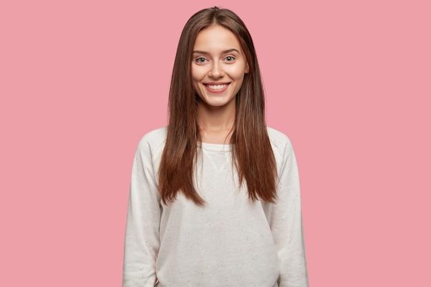 Pojedyncze ujęcie przyjemnie wyglądającej wesołej pięknej brunetki stwarzających na różowej ścianie