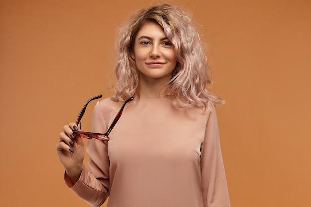Pojedyncze ujęcie radosnej pięknej młodej kobiety rasy kaukaskiej z obszerną fryzurę będąc w dobrym nastroju, trzymając stylowe okulary i uśmiechając się