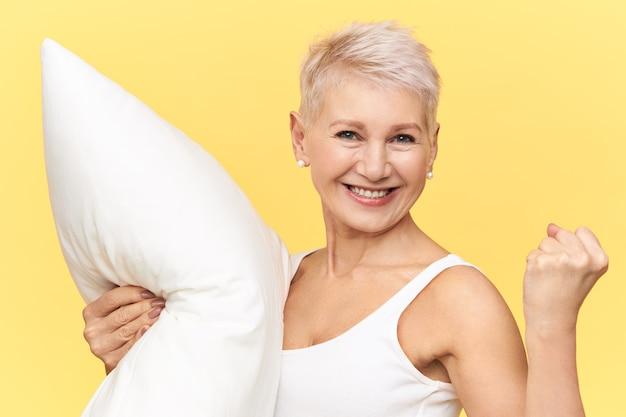 Pojedyncze ujęcie radosnej, podekscytowanej dojrzałej europejki zaciskającej pięść, niosącej poduszkę z białego pióra, czującej się pełną energii, gdy dostała wystarczająco dużo snu, patrzącej w kamerę z promiennym, żywym uśmiechem