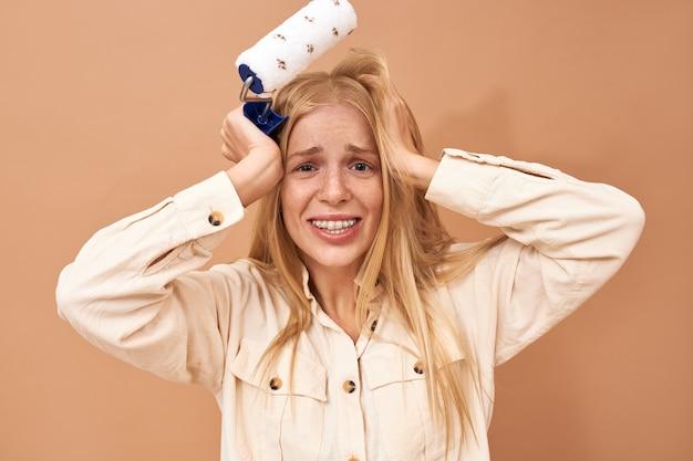 Pojedyncze ujęcie sfrustrowanej, nieszczęśliwej młodej dekoratorki z klamrami trzymającej ręce na głowie, zestresowanej mimiką twarzy, ponieważ nie kończy naprawy na czas