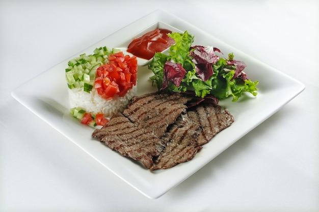Pojedyncze ujęcie steku wołowego z ryżem, sałatą i sałatą - idealne na blog kulinarny lub do menu