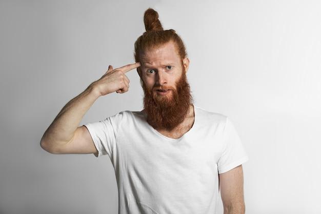 Pojedyncze ujęcie studyjne wkurzonego młodego nieogolonego mężczyzny z kokiem do włosów w białej koszulce, wskazującego palcem wskazującym na głowę, reagującego z oburzeniem na szalony pomysł lub bzdury, mówiąc: czy zwariowałeś