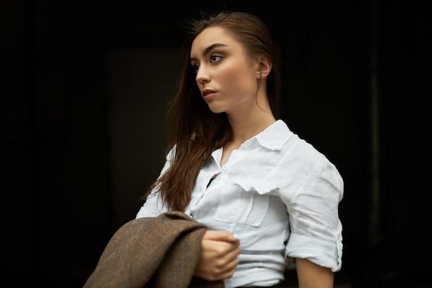 Pojedyncze ujęcie stylowej pięknej młodej kobiety w białej koszuli stwarzających na czarnym tle, trzymając kurtkę, czekając na taksówkę na zewnątrz, mając poważny wyraz twarzy.
