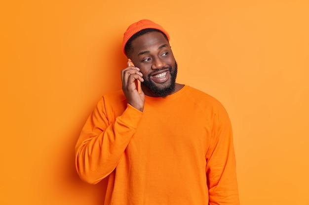 Pojedyncze ujęcie szczęśliwego brodatego mężczyzny prowadzi wesołą rozmowę przez telefon komórkowy skoncentrowany na boku, uśmiechając się radośnie, nosi kapelusz i sweter pozuje na pomarańczowej ścianie studia
