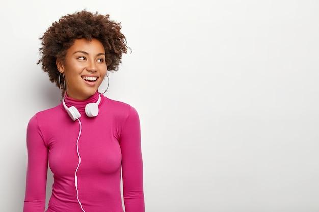 Pojedyncze ujęcie szczęśliwej młodej kobiety afroamerykanów z chrupiącymi włosami, odwraca wzrok z zadowolonym wyrazem, nosi kolczyki i różowy golf, odizolowane na białym tle, używa słuchawek stereo