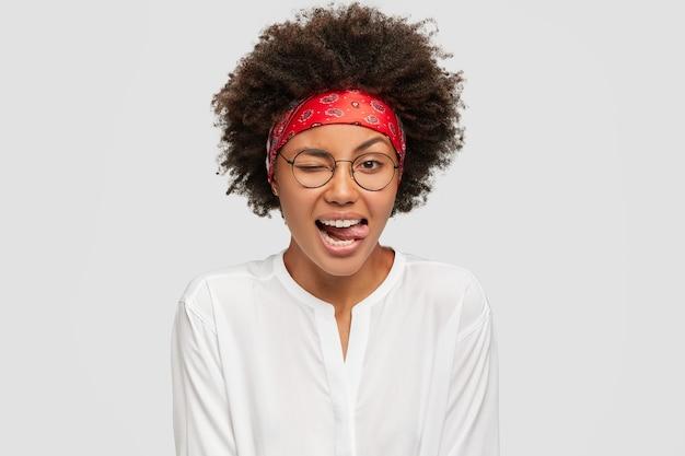 Pojedyncze ujęcie treści piękna dziewczyna miga oczami, wbija język, nosi czerwoną opaskę