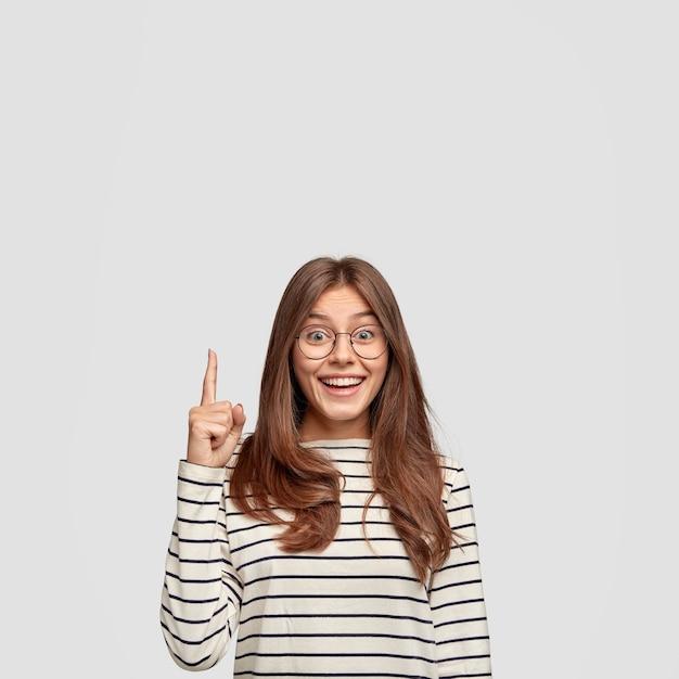Pojedyncze ujęcie wesołej kobiety rasy kaukaskiej z prostymi włosami, pokazuje wolną przestrzeń, wskazuje palcem wskazującym na treść reklamową, nosi swobodny sweter w paski, odizolowany na białej ścianie