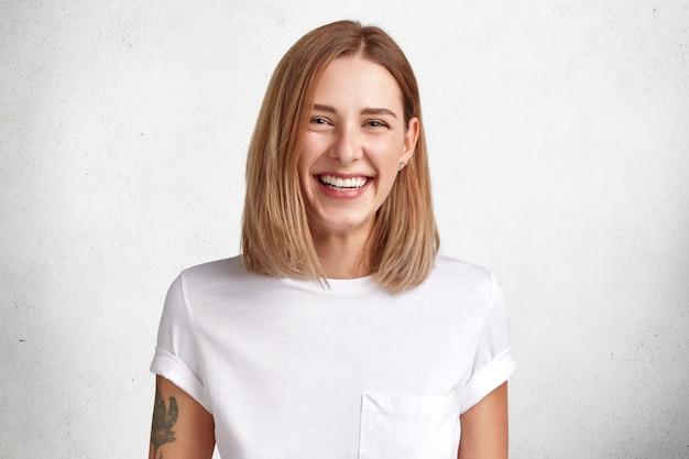 Pojedyncze ujęcie wesołej zadowolonej młodej kobiety o przyjemnym wyglądzie, szerokim uśmiechu, wytatuowanym ramieniu, ubrana w casualową białą koszulkę, pozuje w studio, zadowolona z osiągnięcia sukcesu w pracy i życiu