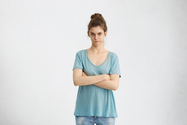 Pojedyncze ujęcie wściekłej żony trzymającej się za ręce, mając sceptyczny i niezadowolony wygląd
