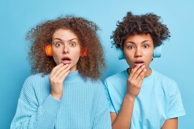 Pojedyncze ujęcie wstrząśniętych dwóch młodych, zróżnicowanych kobiet dyszeć ze zdumienia trzymać usta otwarte ze zdziwienia nosić słuchawki stereo na uszach słuchać muzyki odizolowanej na niebieskiej ścianie. omg koncepcja