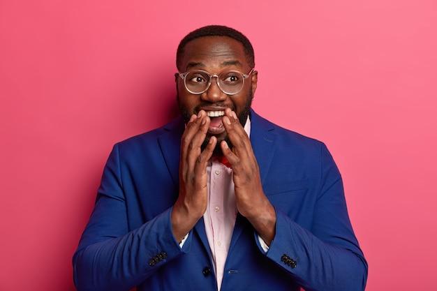 Pojedyncze ujęcie zabawnego przedsiębiorcy płci męskiej chichocze radośnie, próbuje ukryć śmiech, omawia sekrety sukcesu