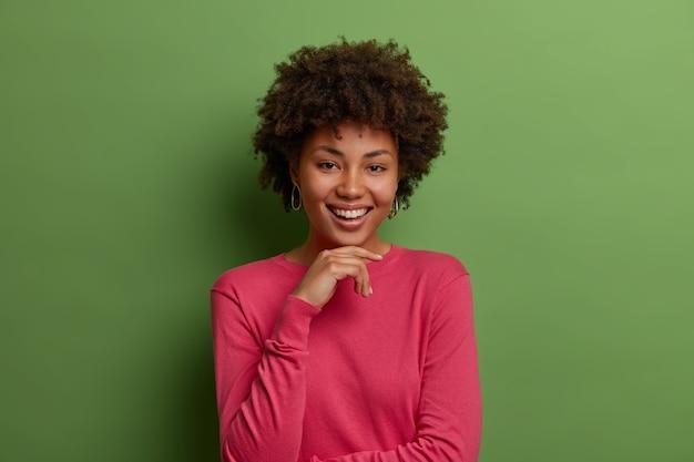 Pojedyncze ujęcie zadowolonej ciemnoskórej afroameryki kobiety trzyma rękę pod brodą, uśmiecha się delikatnie, nosi swobodny różowy sweter, pozuje przy zielonej ścianie, słyszy coś zabawnego, wygląda na zadowolonego
