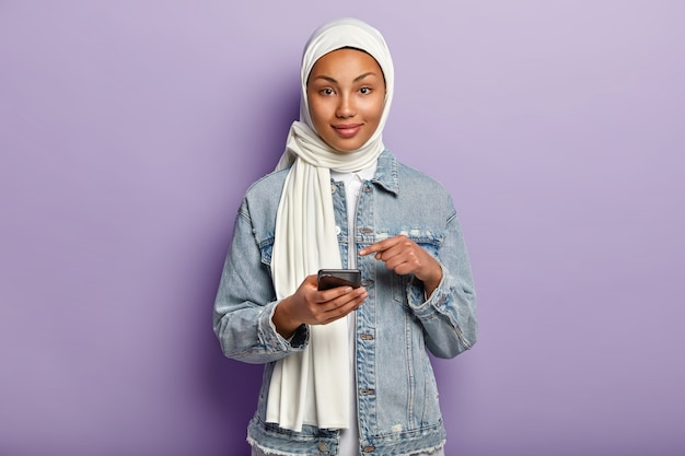 Pojedyncze ujęcie zadowolonej młodej kobiety rasy mieszanej o ciemnej skórze, wyznającej religię muzułmańską, wskazuje na ekran telefonu komórkowego, prosi o przeczytanie wiadomości internetowych na stronie internetowej, odizolowane na fioletowej ścianie.